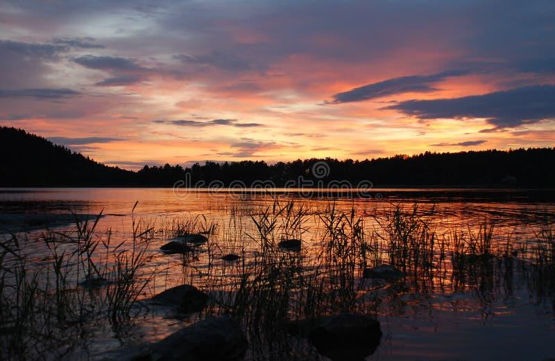 橙色日落多云天空反射湖 免版税库存照片