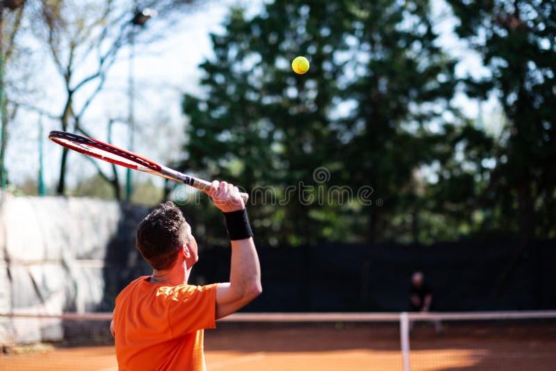 橙色服务的网球员与在空中和别的球 图库摄影