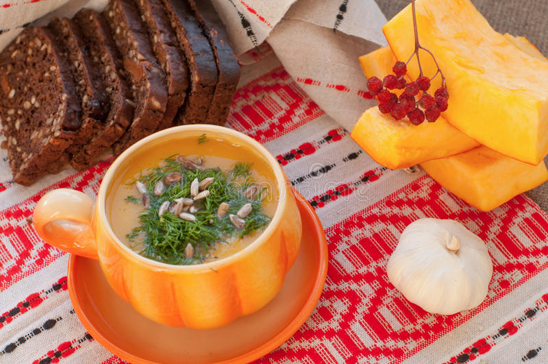 橙色杯子南瓜汤,几个新鲜的南瓜切片黑麦面包,片断和大蒜 免版税库存照片