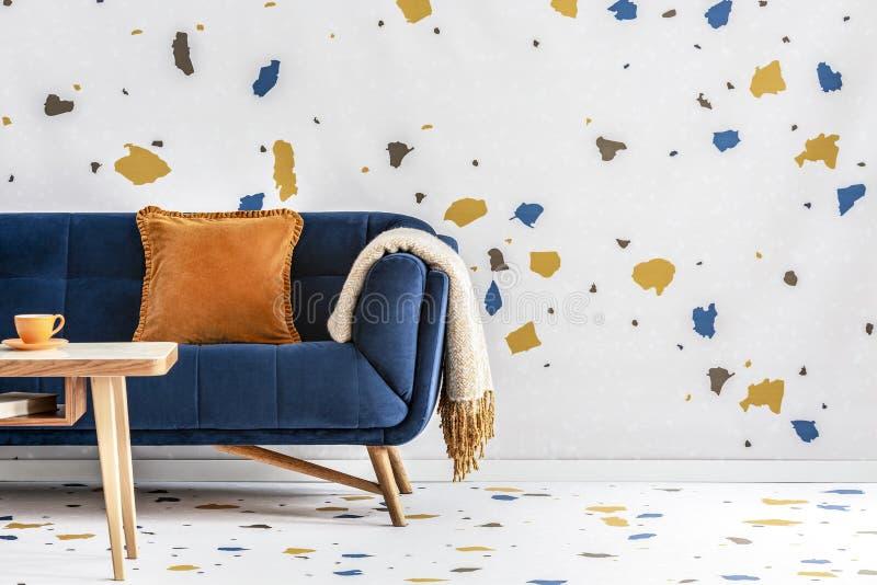 橙色枕头和毯子在藏青色沙发在五颜六色的客厅内部与桌 实际照片 图库摄影
