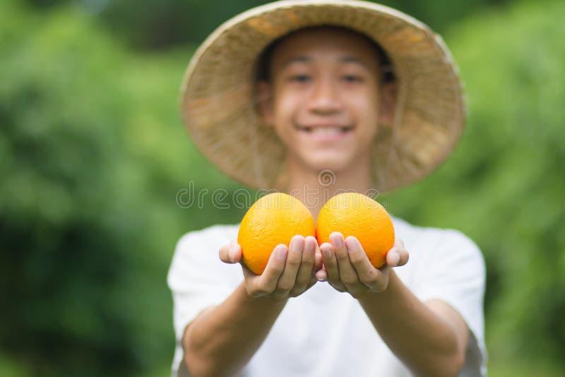 橙色果子新鲜的产品在手边与微笑年轻农夫 免版税库存照片