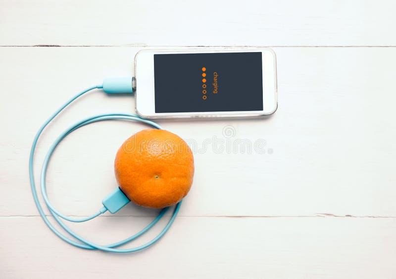 从橙色果子,聪明和环境F的智能手机充电的电池 图库摄影