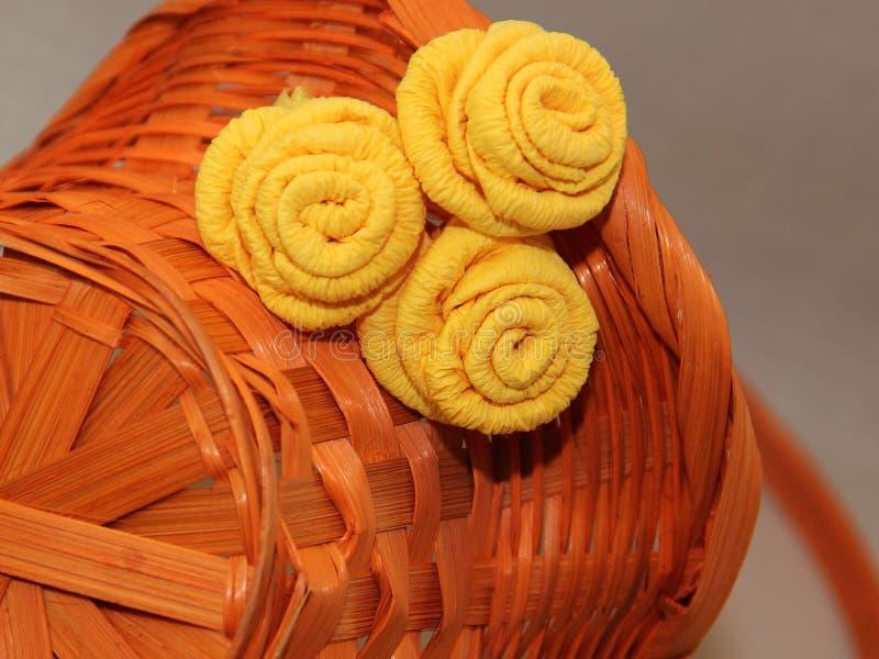 橙色柳条筐在用黄色纸玫瑰装饰的它的边说谎 免版税库存照片