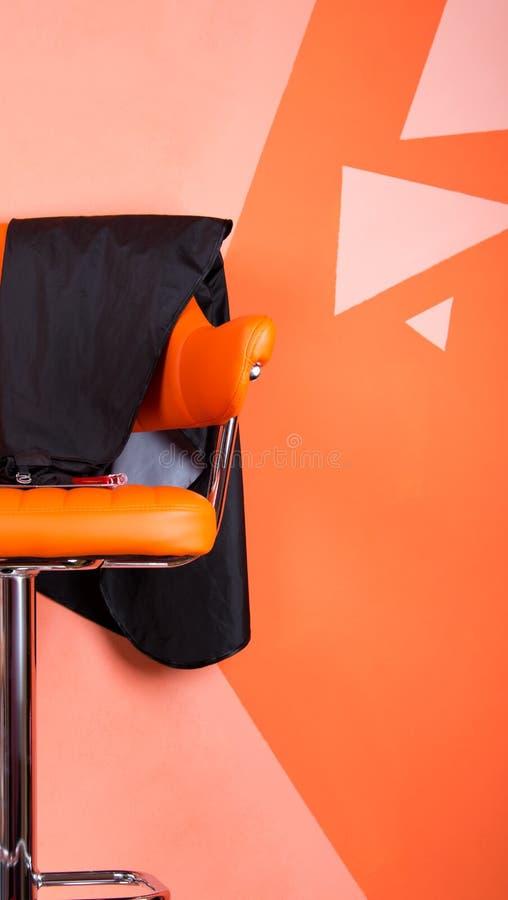 橙色椅子站立对在美容院,美发师的墙壁 库存照片
