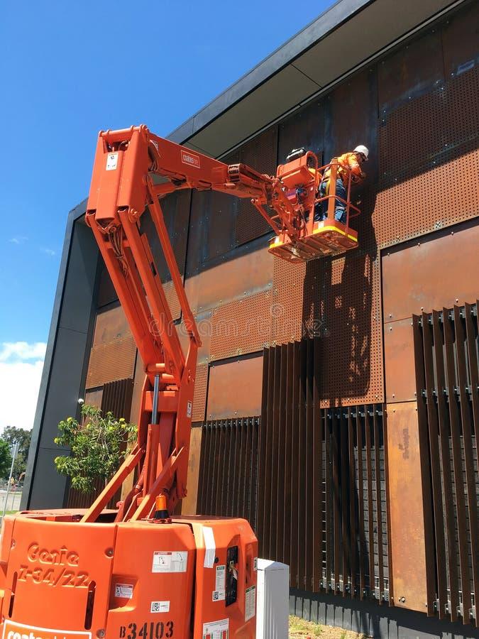 橙色樱桃捡取器起重机的维护工作者 免版税库存照片
