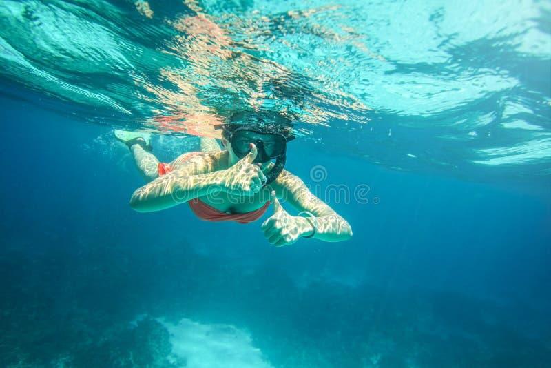 橙色比基尼泳装和水肺面具的少妇 免版税库存照片