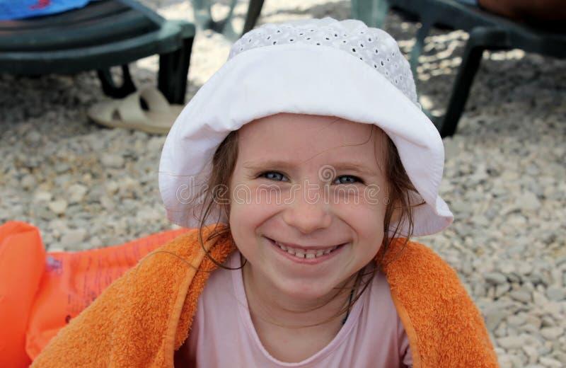 橙色毛巾的微笑的女孩 免版税库存照片