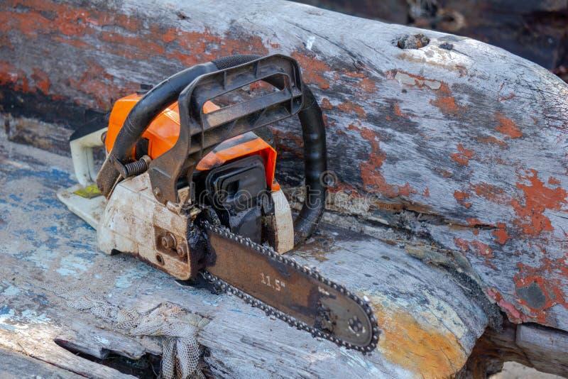 橙色汽油发动机便携式的锯投入了老木板条 图库摄影
