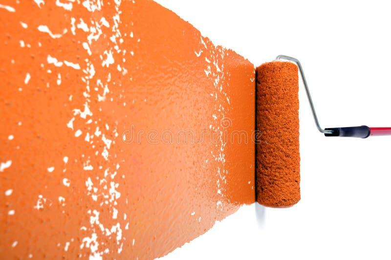 橙色漆滚筒墙壁白色 库存照片