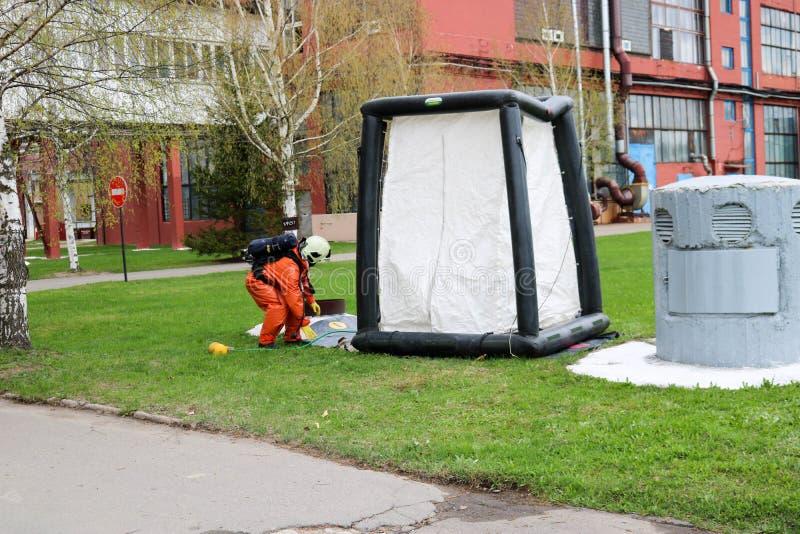 橙色特别防火衣服的一名专业消防队员准备装配一个白色氧气帐篷对抢救人在chem 免版税库存照片