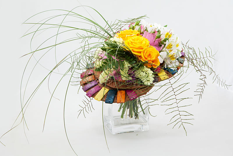 橙色玫瑰、金丝桃属植物和蕨的花卉构成 在一个透明玻璃花瓶的花的布置 查出在白色 图库摄影