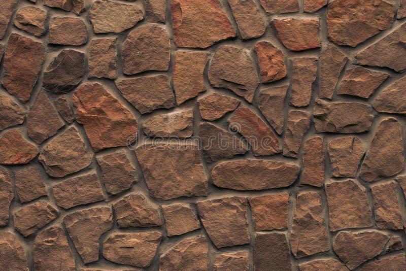 橙色石墙 明亮的棕色岩石纹理 红色在设计的石墙背景上雕琢平面 现代建筑学,花岗岩结构 库存照片