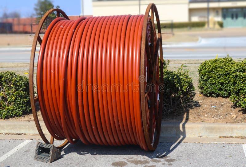 橙色缆绳巨大的卷坐沿街道的地下电缆安装的 图库摄影