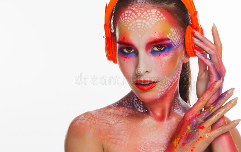 橙色耳机的聪慧的美丽的妇女 图库摄影