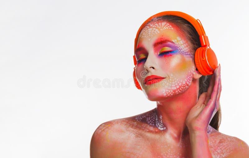 橙色耳机的聪慧的美丽的妇女 免版税库存图片