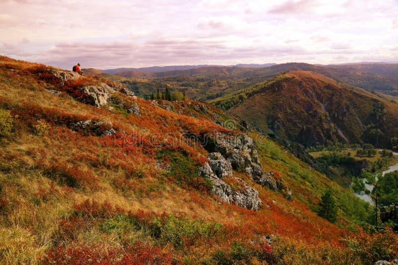 橙色背心的孤独的游人在 natu的小山顶部坐 免版税库存图片