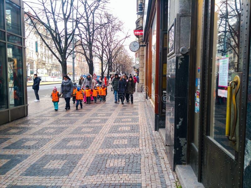 橙色背心的孩子走在布拉格的中心的 免版税库存图片