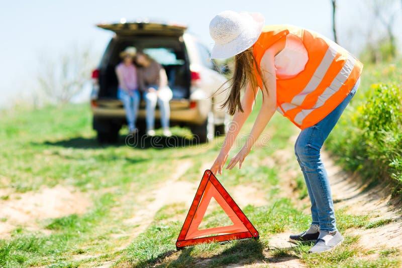 橙色背心设定故障三角的少女在一辆残破的汽车附近站立 免版税库存图片