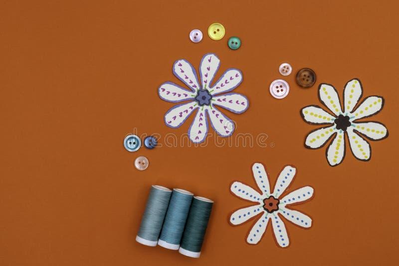 橙色背景上带缝纫钮和线的缝纫概念 免版税图库摄影