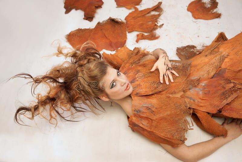 橙色花梢成套装备的妇女,躺下,时尚,演播室 免版税库存图片