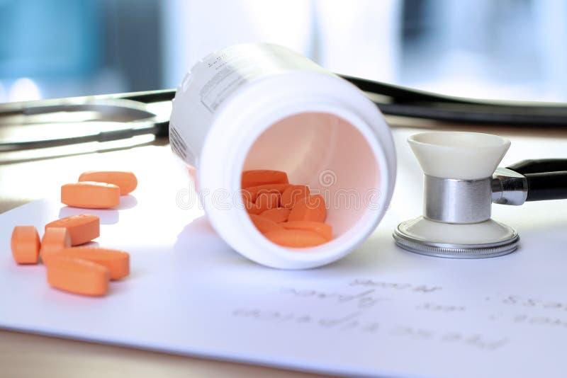 橙色药片、处方和phonendoscope在一蓝色backgrou 免版税库存照片