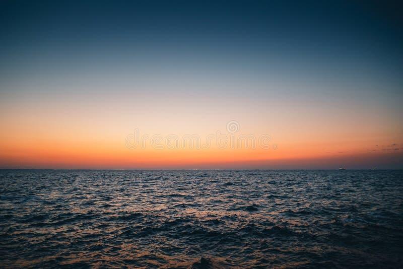 橙色蓝色日出天空,在海水,日落背景上的黎明 图库摄影