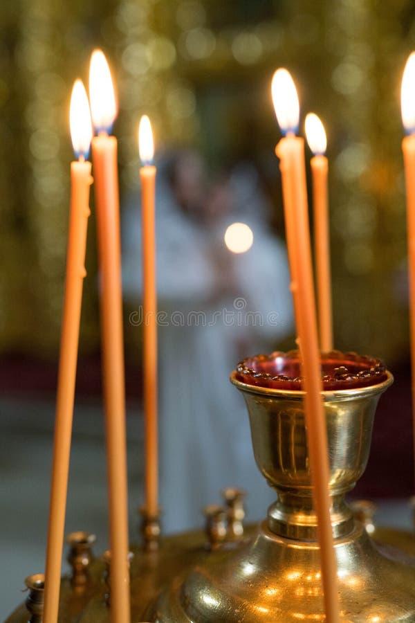 橙色蜡烛在铁烛台站立,并且火被点燃 免版税库存图片