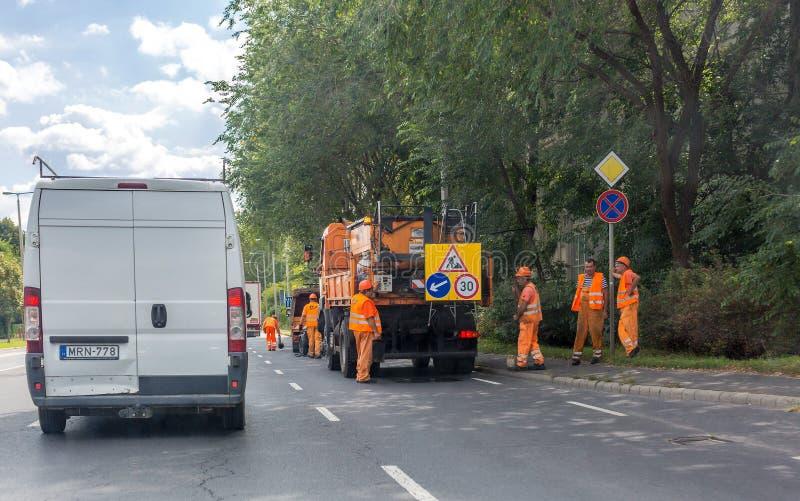 橙色衣服的橙色汽车和旅团路修理工作者在高速公路 柏油路工作者修理路 免版税库存图片