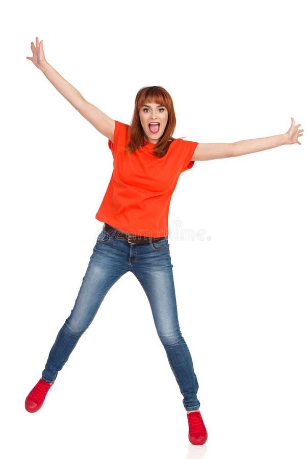 橙色衬衣、牛仔裤和红色运动鞋的愉快的年轻女人在一条腿站立,握胳膊被伸出和呼喊 充分 库存照片
