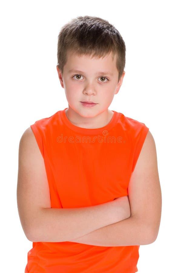橙色衬衣的体贴的男孩 免版税库存照片