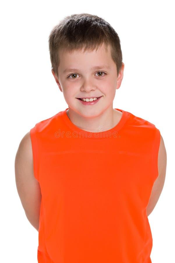 橙色衬衣的微笑的年轻男孩 免版税库存图片