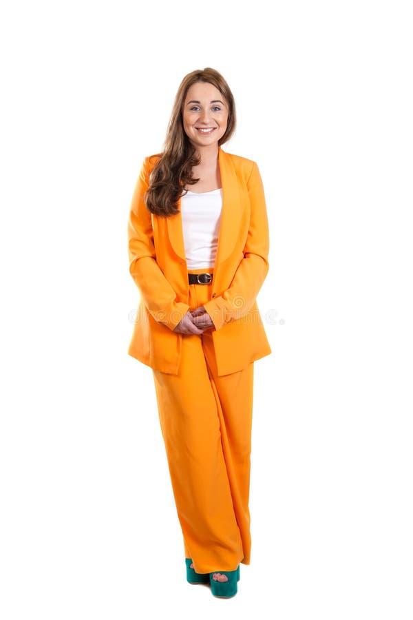 橙色裤子衣服的微笑的女孩 免版税库存图片