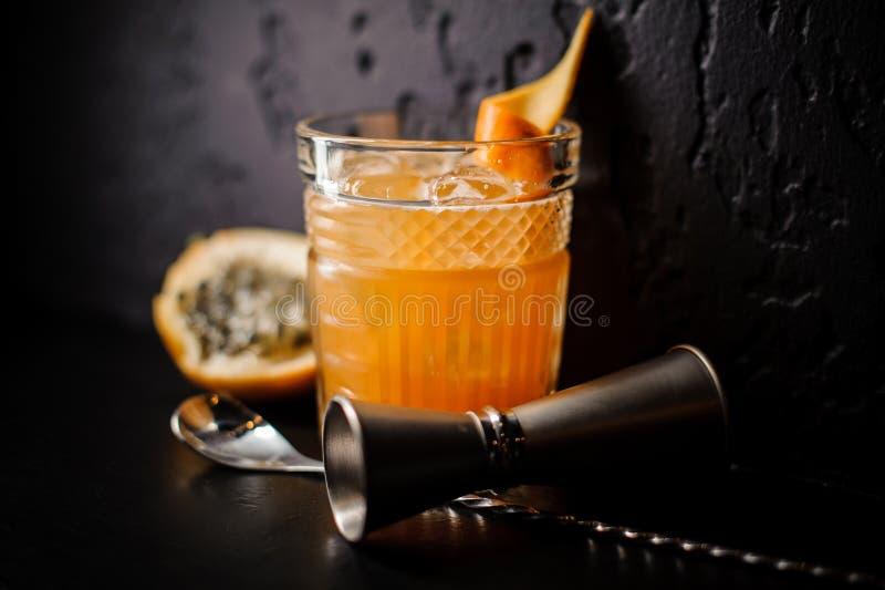 橙色颜色酒精鸡尾酒与冰和柑橘的在黑背景站立 免版税库存图片