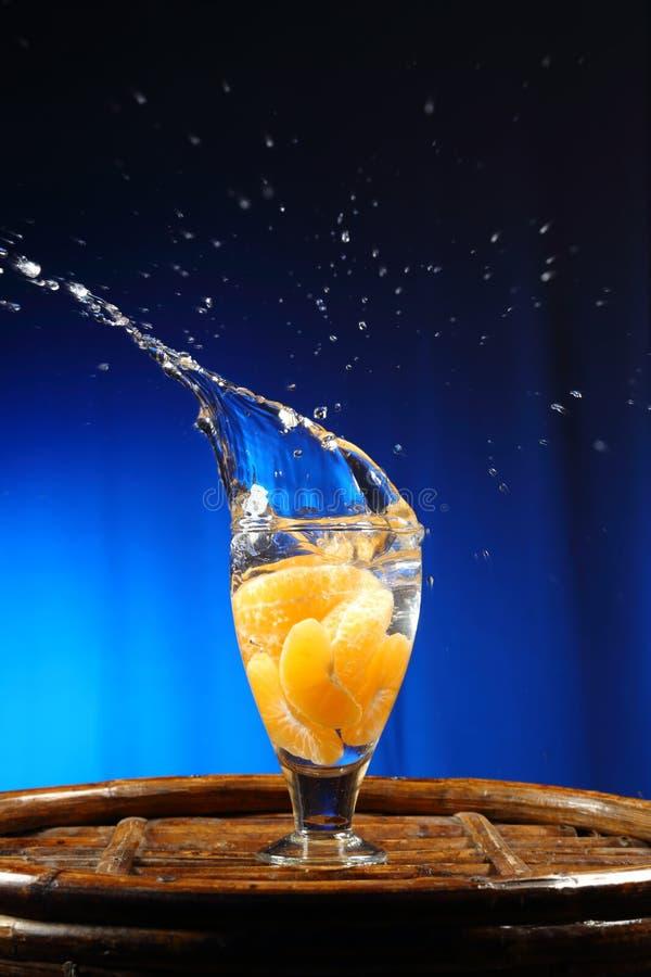 橙色飞溅到杯水 库存图片