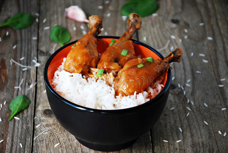 橙色鸡大腿用在碗的米 免版税库存图片