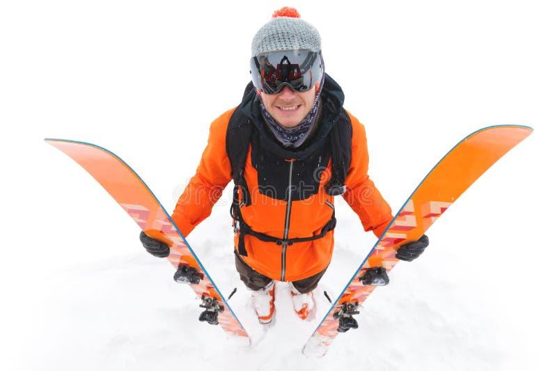 橙色黑衣服的一位专业滑雪者运动员与与滑雪的黑滑雪帽在他的与a的手立场 免版税库存照片