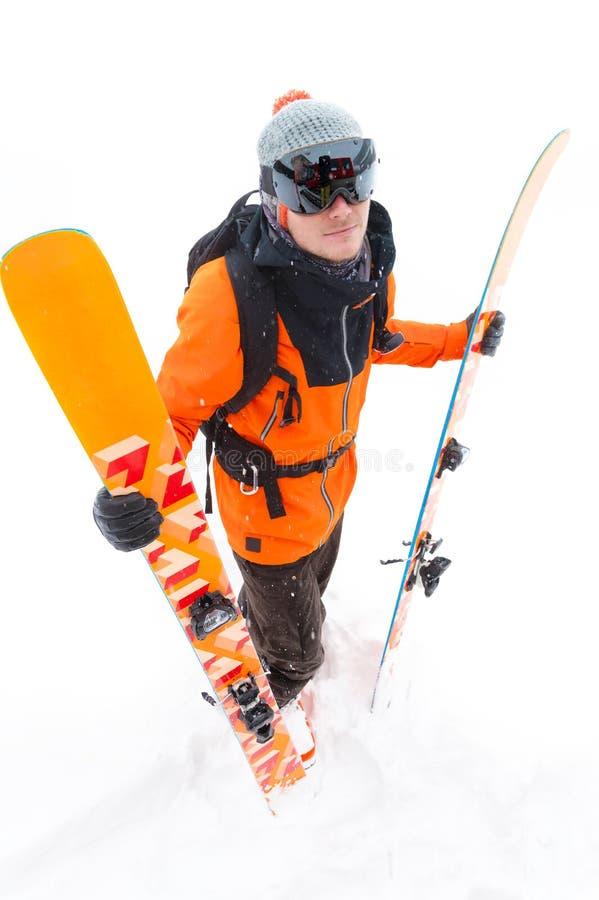 橙色黑衣服的一位专业滑雪者运动员与与滑雪的黑滑雪帽在他的与a的手立场 免版税库存图片
