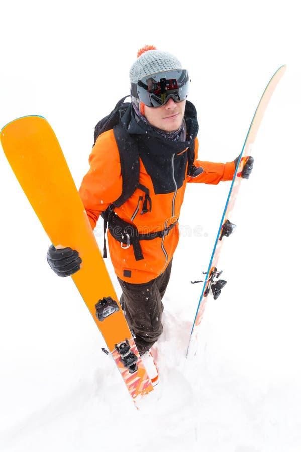 橙色黑衣服的一位专业滑雪者运动员与与滑雪的黑滑雪帽在他的与a的手立场 库存照片