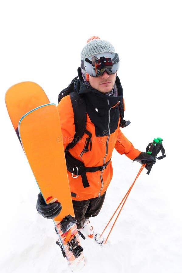 橙色黑衣服的一位专业滑雪者运动员与与滑雪的黑滑雪帽在他的与a的手立场 库存图片