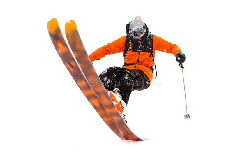 橙色黑衣服的运动员滑雪者获得成功在滑雪背面 在山做的真正的照片 免版税库存照片