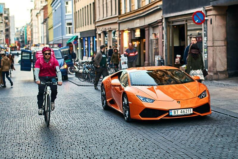 橙色Lamborghini Huracan LP 580-2 Spyder汽车在有自行车传讯者的街道上发布了大约2016年在意大利停放了 库存图片