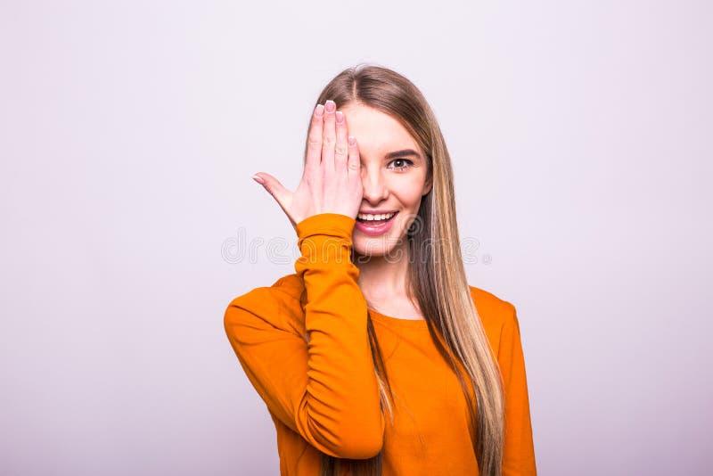 橙色T恤杉关闭的一白肤金发的女孩注视用在白色的手 库存图片