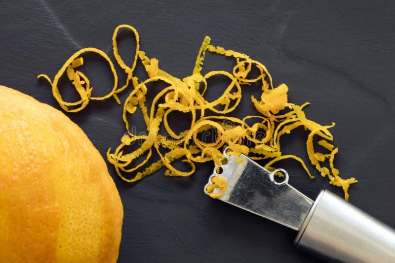 橙风味和Zester顶视图在黑暗的板岩 图库摄影