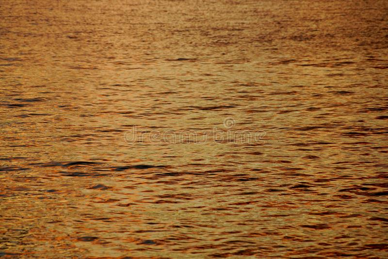 橙黄海洋水波纹树荫在离奥阿胡岛反射的黄昏的附近北部岸点燃 库存照片