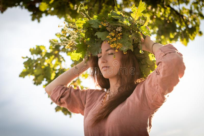 橡木叶子和花花圈的女孩在树下 库存图片
