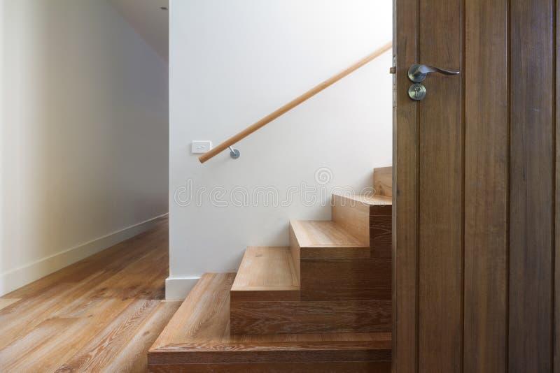 橡木现代楼梯在水平的前门旁边的 图库摄影