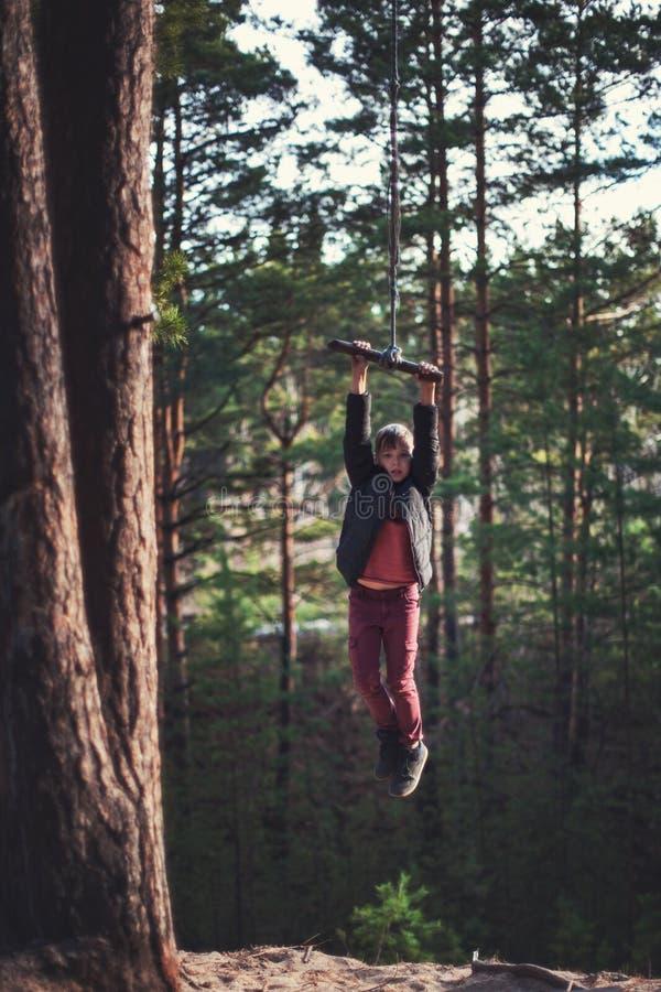 橡皮筋的青少年的男孩在秋天森林里 免版税库存图片