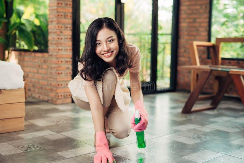 橡胶手套贩卖商的亚裔妇女与布料和洗涤剂喷洒clea 免版税库存图片