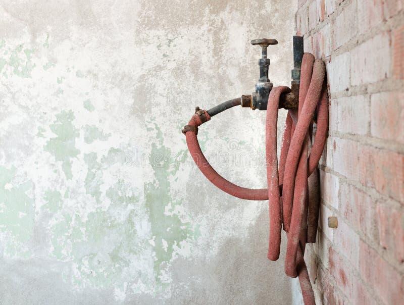 橡胶水管老减速火箭的水起重机和卷  免版税库存图片