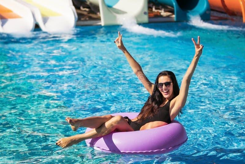 橡胶环的俏丽的女孩在游泳池 免版税图库摄影